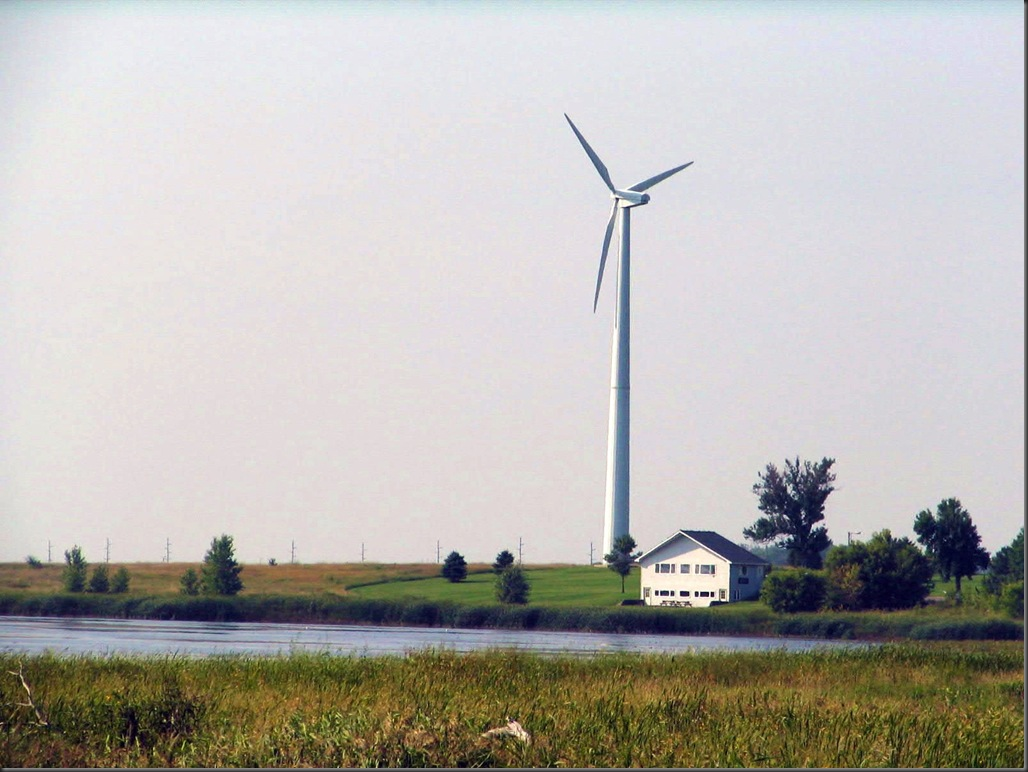 Tall wind turbine behind a country house in Minnesota.
