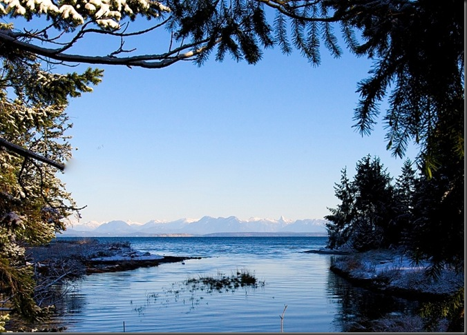 Black Creek, Vancouver Island entering Georgia Straight with the BC's Coastal Mountain Range in the distance - by Charles A.E. Brandt
