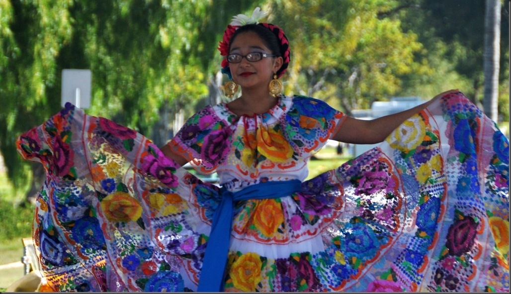 Girl dancing in a colorful costume on day of the dead